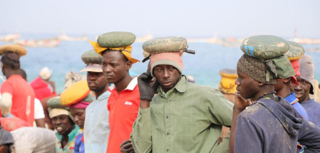Des porteurs de poisson attendent le débarquement